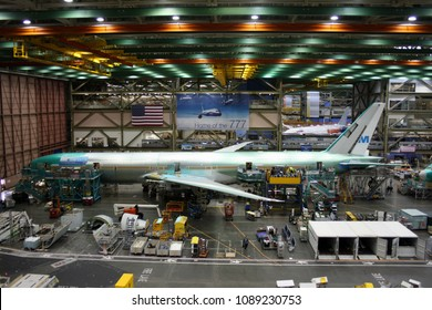 EVERETT (WA), USA – JANUARY 30 2015: Unidentified Boeing employees continue work building a Boeing 777 jets at its Everett factory, including for KLM Royal Dutch Airlines with a Boeing 787 behind.