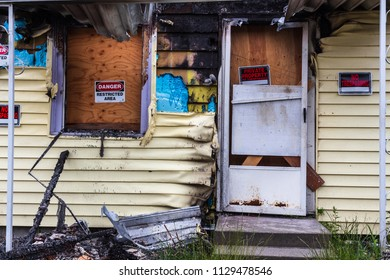Everett, WA / USA / July 1, 2018: Melted and rusty screen door hangs in front entry after a house fire