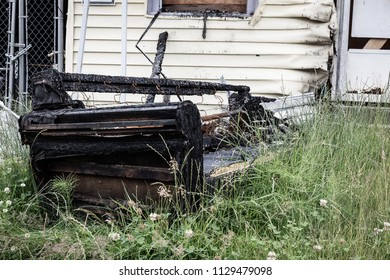Everett, WA / USA / July 1, 2018: Burned couch that is in front of a house that caught fire.