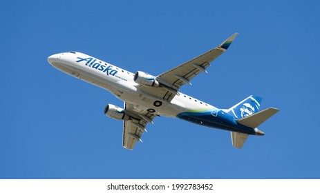 Everett, WA, USA - June 16, 2021; An Alaska Horizon Horizon Embraer ERJ 170-200 climbing from Snohomish County Airport against a blue sky.