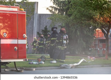 Everett WAshington, USA / 05/09/2019 - House Fire Fireman Try To Contain Fire on Roof on old Ballon Frame Home as personal on ground prepare to go in.
