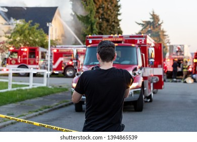 Everett WAshington, USA / 05/09/2019 - House Fire Fireman Try To Contain Fire on Roof on old Ballon Frame Home as a person with camera looks on