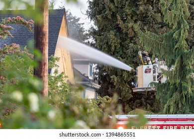 Everett WAshington, USA / 05/09/2019 - House Fire Fireman Try To Contain Fire on Roof on old Ballon Frame Home