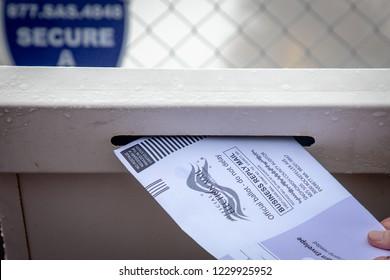 Everett, Washington / USA - 10/27/2018 - Putting a mail in ballot into the drop off ballot box