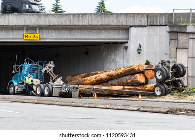 Everett, Washington, USA - June 25, 2018. Police officers inspect a logging truck accident.