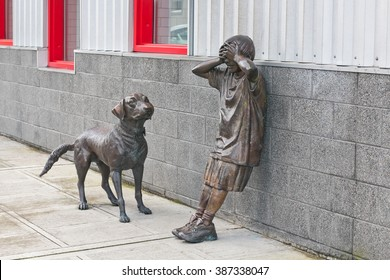 "Everett, Washington, USA. March 06 2016: ""Hide and Seek"" boy and dog statues outside the Children's Museum Everett."