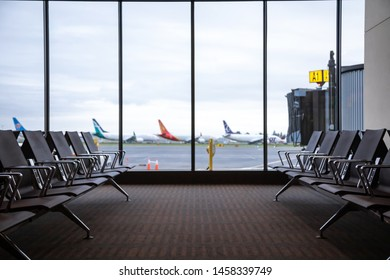 Everett, Washington / USA - May 25 2019: Foreground focus on seats in the terminal waiting area at the new Paine Field Airport, with blurry airplanes on the tarmac in the distance and space for text