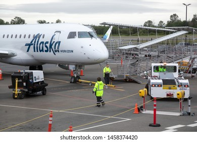 Everett, Washington / USA - May 25 2019:  Ground crew working on an Alaska Airlines airplane on the tarmac at the new Paine Field Airport north of Seattle