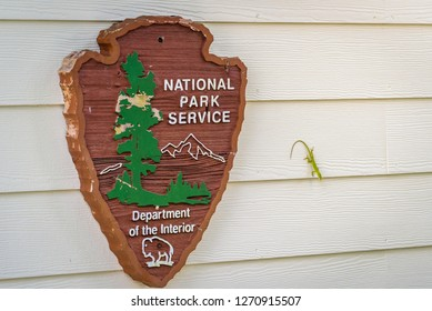 Everglades National Park, Florida - December 2018. Entrance sign to Ernest F. Coe Visitor Center by the National Park Service - Department of the Interior with a small green lizard next to it.