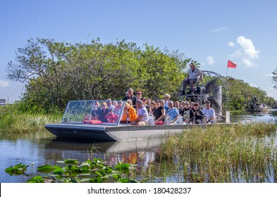 EVERGLADES, UNITED STATES - NOVEMBER 30, 2013: group of  tourists riding an airboat. The Everglades are a natural region of wetlands in the southern portion of the U.S. state of Florida.