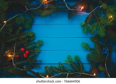 Evergreen branch with Christmas light on blue boards