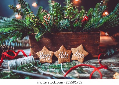 Evergreen Christmas centerpiece with Happy holidays gingerbread cookies and lights