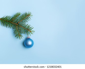 Evergreen coniferous tree  with blue Christmas ball on blue background. New Year greeting card with place for text.