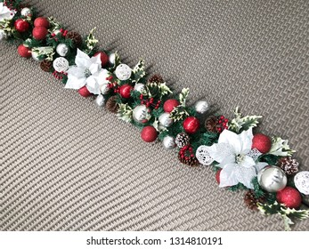 Evergreen twigs of Christmas tree, poinsettia flower, berries and holiday decorations in a garland. Flat lay. Top view.