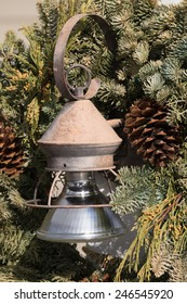 Evergreen wreath with old rusty lamp and pine cones