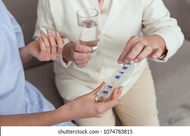 Every day. Close up of senior female hands receiving drugs from female hands that holding container