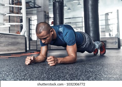 Every day routine. Handsome young African man in sport clothing planking while exercising in the gym
