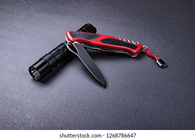 Everyday carry (EDC) items for men - opened folding knife and tactical flashlight on dark silver grey background. Survival set. Minimal concept.