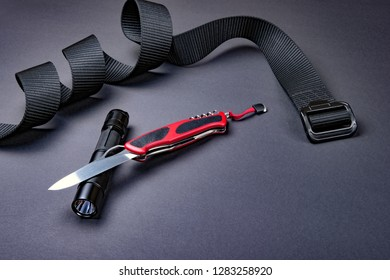 Everyday carry (EDC) items for men - opened folding knife, tactical flashlight and black  belt on dark silver grey background. Survival set. Minimal concept.