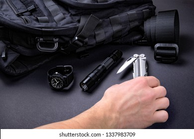 Everyday carry (EDC) items for men in black color - backpack, tactical belt, flashlight,  watch and silver multi tool in men's hand. Survival set. Minimal concept.