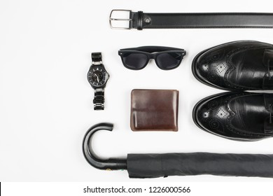 Everyday carry objects on white background. Wallet, wristwatch, umbrella, men's shoes, belt, glasses. Top view. Space for text
