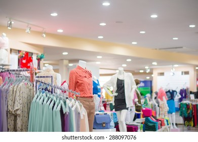 Everyday dressed woman mannequins and hangers with blouses in store