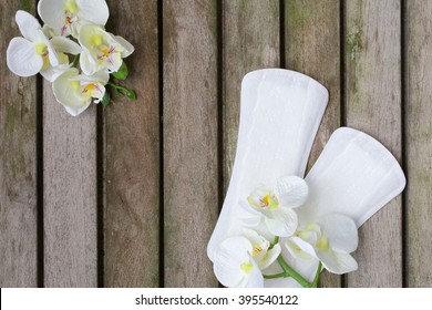 Everyday female pantyliners with artificial orchids heads on a wooden surface covered by moss. Background.
