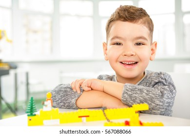 Everyday fun time. Cute happy little boy smiling joyfully to the camera while playing colorful bricks in front of him copyspace toys leisure education creativity learning happiness childhood concept