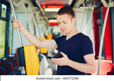 Everyday life and commuting to work by bus (tram). Handsome man is paying transport ticket with mobile phone.