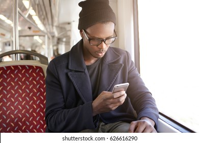 Everyday life, people and modern technology. Stylish serious handsome young Afro American designer wearing glasses, hat and coat commuting to work by bus or tram, checking e-mail on mobile phone