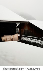 Everyday life scene with cottages covered with snow in the Austrian alps without decoration
