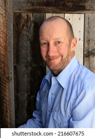 Everyday man in a blue shirt with a wooden background.