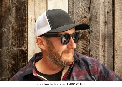 Everyday man with hat and sunglasses by a barn wood wall.