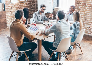 Everyday meeting. Group of six young people discuss something and gesturing while sitting at the table in office
