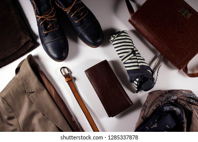 Women's everyday outfit and accessories: shoes, velvet trousers, blazer, leather bag, umbrella, wallet, scarf and belt. Casual clothes flat lay represents modern lifestyle, traveling, urban life.