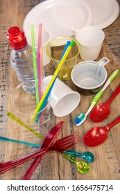 Everyday plastic waste, various plastic utensils, environmental protection on wood background