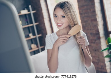 Everyday routine for every woman! Beautiful charming smiling glad joyful gorgeous careless woman in white t-shirt is brushing her healthy long smooth hair in front on mirror in the morning