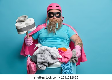 Everyday routine and housekeeping concept. Bearded stout man janitor does laundry at home pose with basin full of dirty clothes holds plunger wrapped with toilet paper isolated on blue background