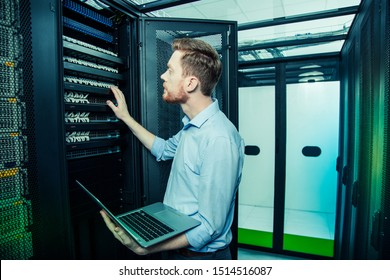 Everyday work. Smart handsome man holding his new laptop while working in the data center