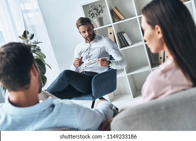 Everyone faces difficulties. Young married couple talking while sitting on the therapy session with psychologist