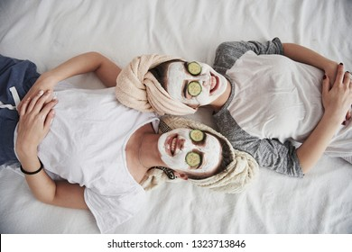 Everyone is smiling. Lying on the white bed. Top view. Conception of skin care by using white mask and cucumbers on the face.