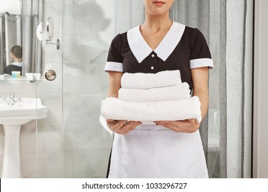 Everything is fresh and clean. Cropped portrait of housecleaner in maid uniform holding pack of white towels. Employee brought everything customer ordered to his hotel room