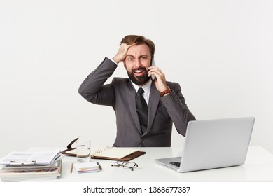 Everything goes wrong, OMG, it's a disaster! Dressed in a suit respectable office worker sitting at desktop grasping his head panics, nervous, is in a difficult situation, holding a phone near his ear