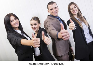 Everything is good. Successful young business team giving thumbs up.
