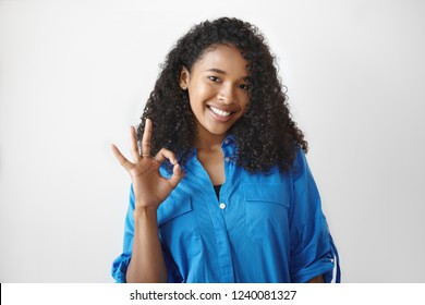Everything is great. Pretty girl of mixed race appearance showing ok gesture, saying that she is doing okay. Attractive African female in good mood gesturing in studio, smiling friendly at camera