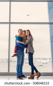 Everything looks great. Full height shot of beautiful caucasian family looking at camera at airport while waiting for boarding