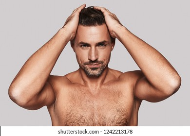 Everything must be perfect. Charming young man keeping hands in hair and smiling while standing against grey background