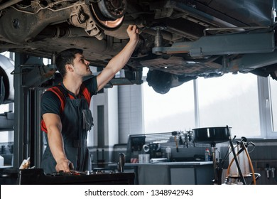 Everything must be perfect. Man at the workshop in uniform fixes broken parts of the modern car.