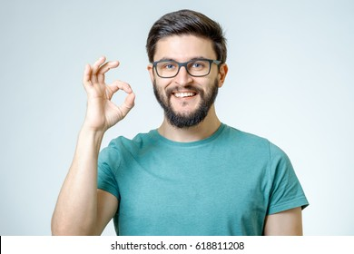Everything is OK! Happy young man gesturing OK sign and smiling against gray background