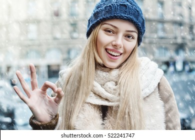 Everything is OK! Outdoor close up portrait of young beautiful happy smiling girl showing okay gesture. Model looking at camera, wearing stylish winter clothes.  Christmas, new year, concept. Snowfall